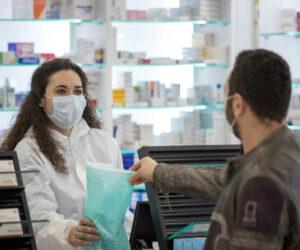 farmacêutica entregando medicamento ao cliente
