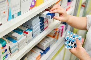 Farmacêutico consultando medicamento na prateleira